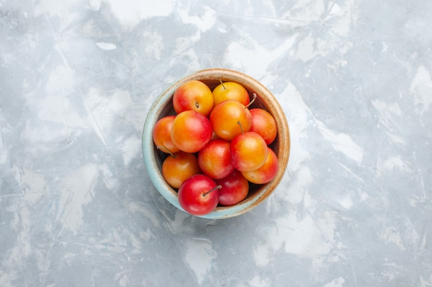 Vista superior ameixas frescas azedas e frescas dentro da panela na mesa de luz fruta azeda fresca suave