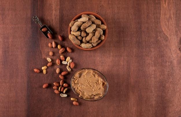 Vista superior amendoins crus e descascados na tigela e manteiga de amendoim na horizontal de madeira