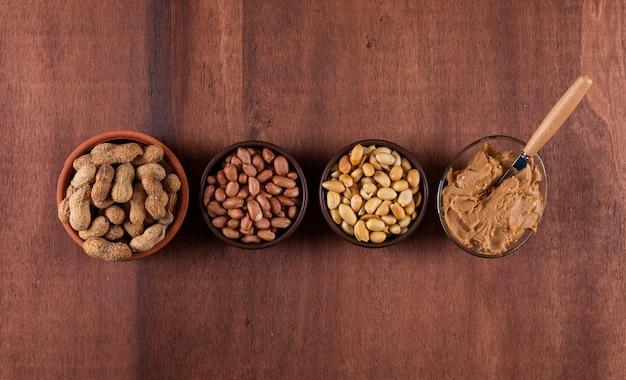 Vista superior amendoins crus na tigela e manteiga de amendoim na horizontal de madeira