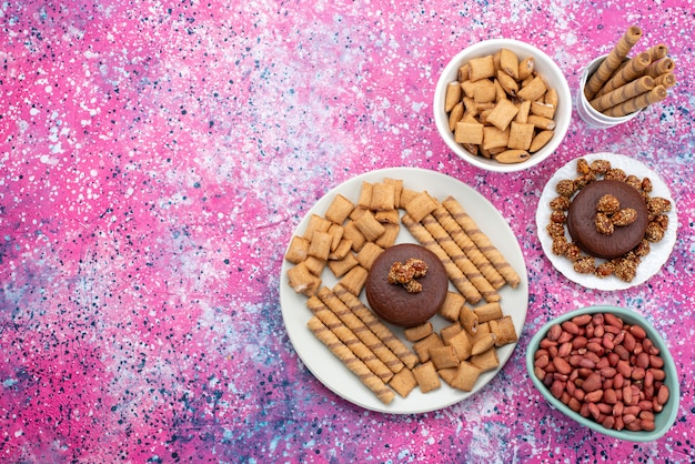 Vista superior amendoins e biscoitos dentro dos pratos no fundo colorido biscoito biscoito açúcar doce cor