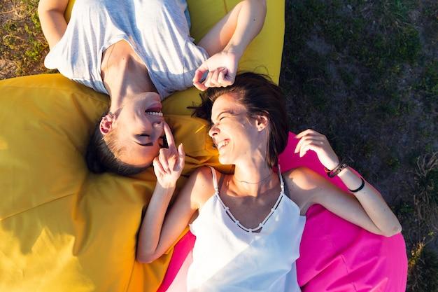 Vista superior amigos sorrindo em pufes coloridos