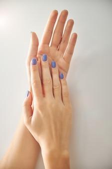 Vista superior ampliada das palmas das mãos e unhas da mulher cobertas com esmalte de gel azul isolado no fundo branco
