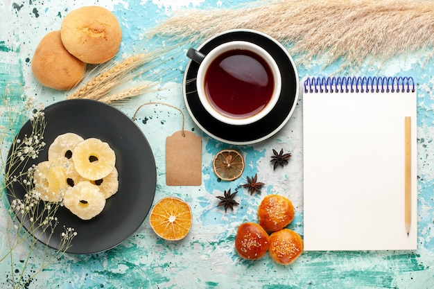 Vista superior anéis de abacaxi secos com xícara de chá e biscoitos no fundo azul bolo assar biscoito de frutas doce biscoito