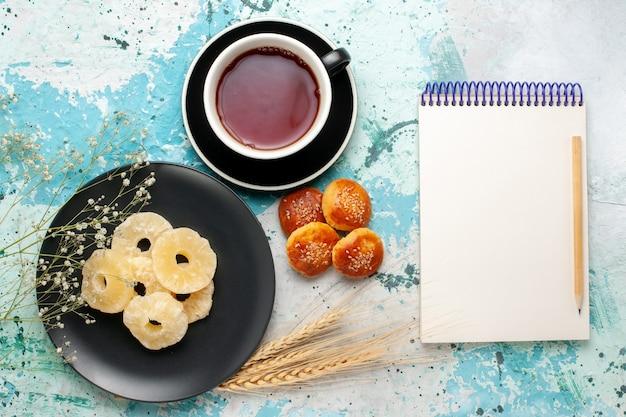 Vista superior anéis de abacaxi secos com xícara de chá e bolinhos no fundo azul fruta abacaxi açúcar doce seco