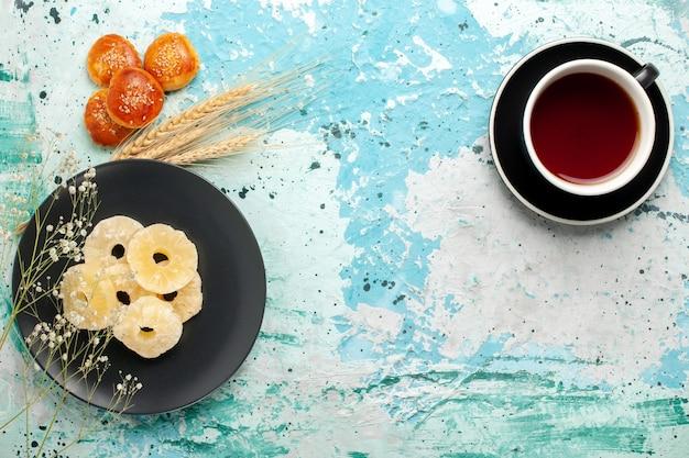Vista superior anéis de abacaxi secos dentro do prato com bolos e chá no fundo azul frutas abacaxi açúcar doce seco