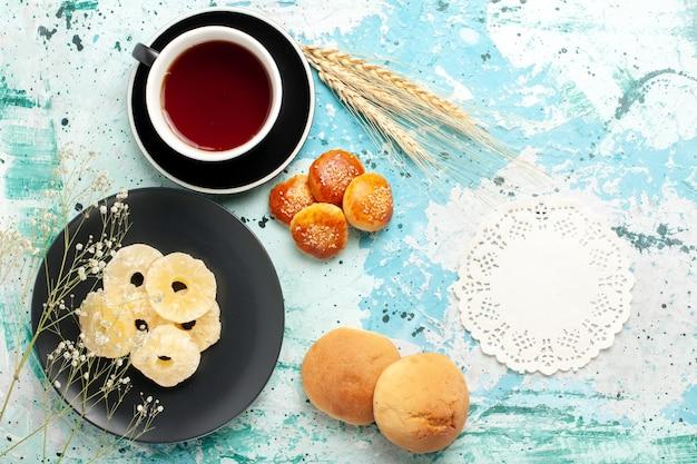 Vista superior anéis de abacaxi secos dentro do prato com bolos e xícara de chá na mesa azul frutas abacaxi açúcar doce seco