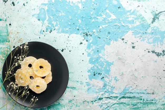 Vista superior anéis de abacaxi secos dentro do prato com fundo azul claro frutas abacaxi açúcar doce seco