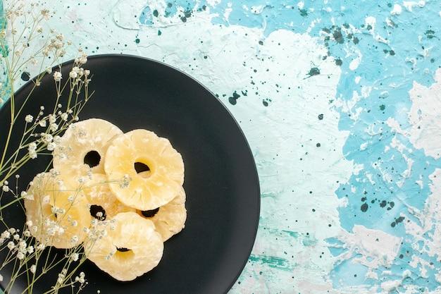 Vista superior anéis de abacaxi secos dentro do prato com fundo azul frutas abacaxi açúcar doce