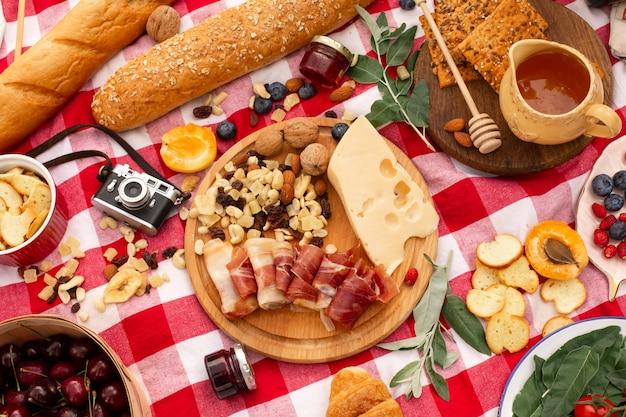 Vista superior ao ar livre de uma placa de degustação de piquenique com pães e pote de mel.