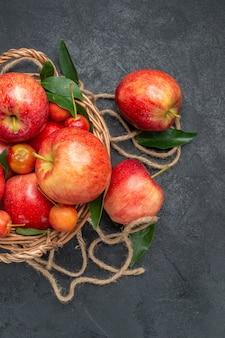 Vista superior ao longe da cesta de frutas das apetitosas cerejas e maçãs com folhas