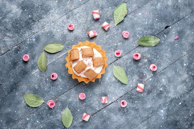 Vista superior ao longe delicioso bolo cremoso com biscoitos e balas fatiadas em cinza