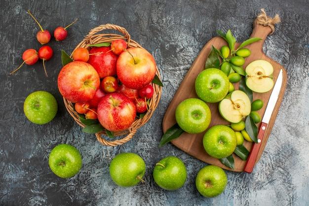 Vista superior ao longe do tabuleiro de maçãs da apetitosa cesta de maçãs verdes com facas de frutas
