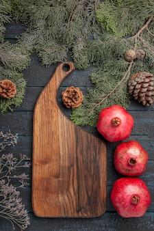 Vista superior ao longe do tabuleiro e romãs romãs maduras ao lado do tabuleiro da cozinha e galhos com cones