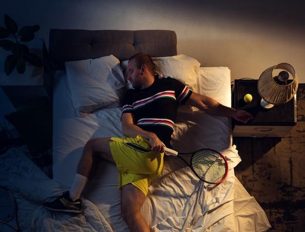 Vista superior apaixonada de um jovem jogador de tênis profissional dormindo em seu quarto em roupas esportivas