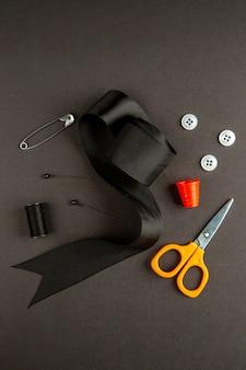 Vista superior arco preto com tesouras e botões em fundo escuro