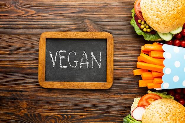 Vista superior arranjo de comida saudável com letras vegan na lousa