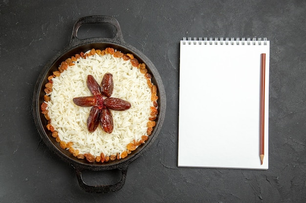 Vista superior arroz cozido com passas dentro da panela na superfície escura comida arroz refeição oriental jantar