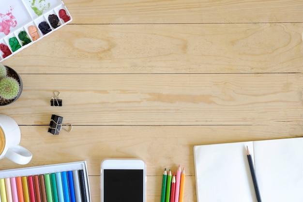 Vista superior artista espaço de trabalho smartphone, cor, caneca de café, papel bloco de notas, cactos e lápis na mesa de madeira