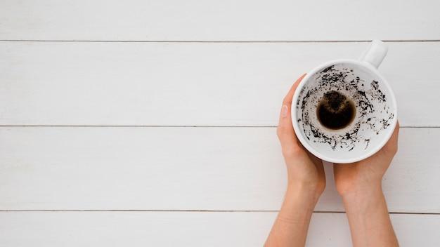 Vista superior as mãos segurando a xícara de café