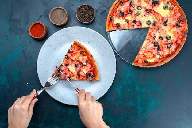 Vista superior assou pizza deliciosa com salsichas de azeitonas e queijo feminino comendo na mesa azul.