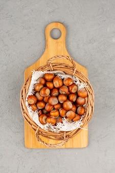 Vista superior avelãs todo dentro da cesta na mesa cinza