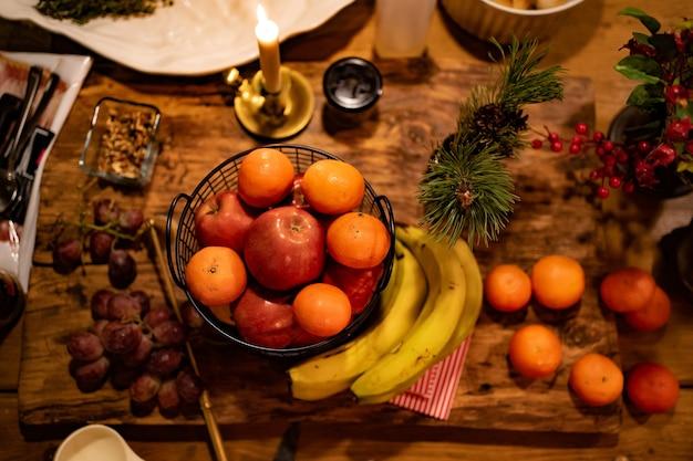 Vista superior. baixa luz .angerinas e maçãs na cesta de metal, queimando velas, uvas, bananas, galho de pinheiro na mesa da cozinha. decoração de ano novo ou natal. jantar à luz de velas no escuro. foco seletivo.