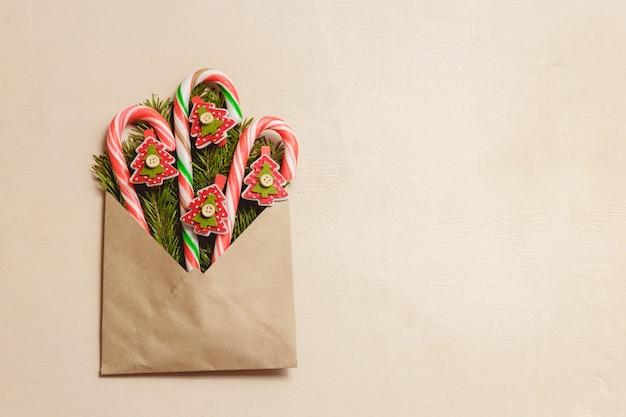 Vista superior, bastões de doces e abeto vermelho em forma de pinos no envelope marrom