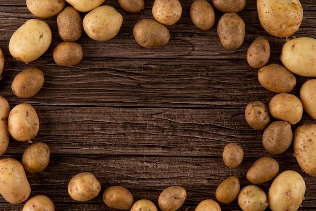 Vista superior batatas cruas, com espaço de cópia no fundo de madeira