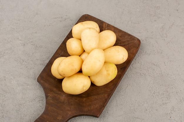 Vista superior, batatas descascadas no chão cinza