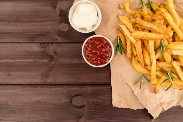 Vista superior batatas fritas com molho na mesa de madeira