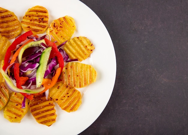 Vista superior batatas grelhadas à esquerda com pepino fresco, pimentão laranja, repolho roxo e espaço de cópia em fundo cinza escuro
