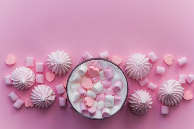 Vista superior bebida quente com chantilly, marshmallows e bombons de chocolate em forma de coração