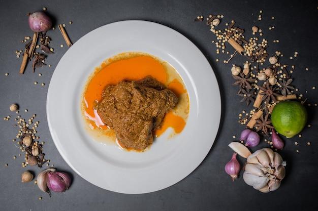 Vista superior beef rendang comida tradicional asiática no prato e fundo preto