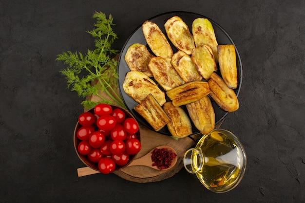 Vista superior, berinjela cozida dentro de chapa preta, juntamente com tomates vermelhos frescos e azeite no chão escuro
