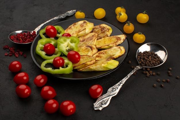 Vista superior, berinjela cozida, juntamente com pimentão verde fatiado e tomate cereja vermelho inteiro dentro de chapa preta no chão escuro