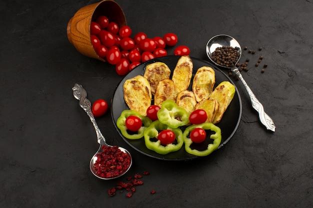 Vista superior, berinjela cozida, juntamente com pimentão verde fatiado e tomates vermelhos inteiros na mesa escura