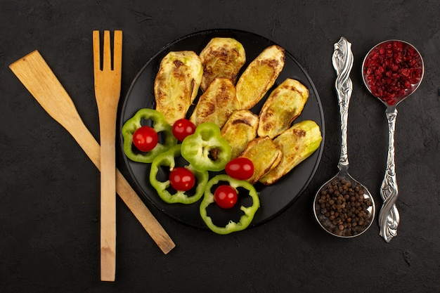 Vista superior, berinjela cozida, juntamente com pimentão verde fatiado fresco e tomate dentro de chapa preta no chão escuro