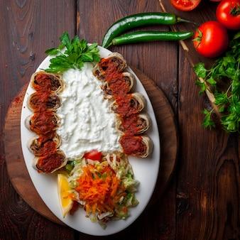 Vista superior beyti kebab com iogurte e salsa e salada em chapa branca