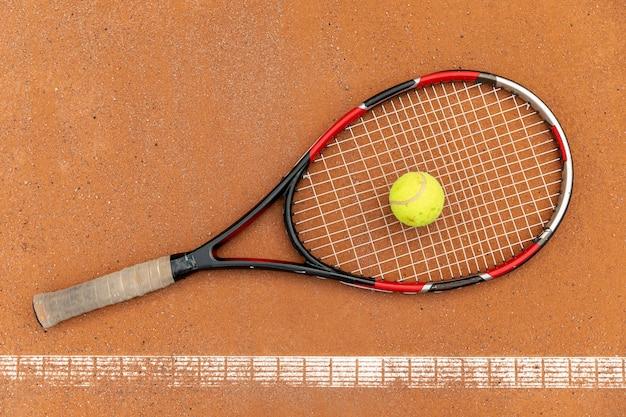 Vista superior bola de tênis com raquete no chão