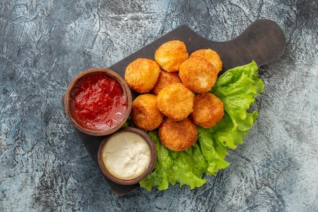 Vista superior bolinhas de queijo frito molhos em tigelas pequenas na mesa de corte vista superior bolinhas de queijo frito tigelas de molho de alface na tábua de cortar