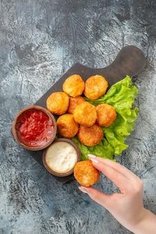 Vista superior bolinhas de queijo frito tigelas de molho de alface na tábua de cortar bolinha de queijo em mão feminina na mesa