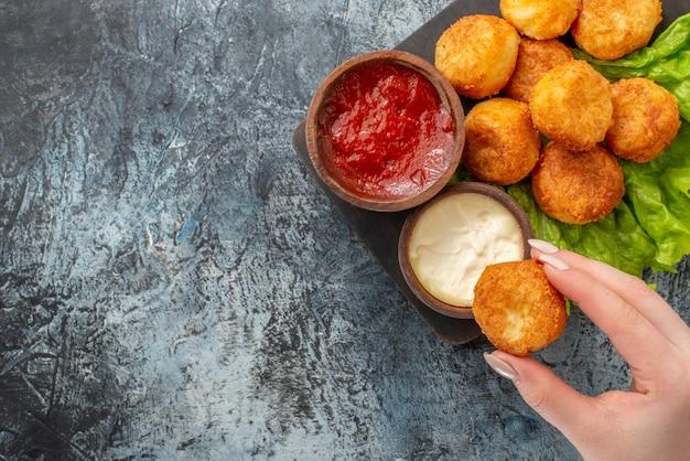 Vista superior bolinhas de queijo frito tigelas de molho de alface na tábua de cortar bolinha de queijo na mão da mulher na mesa