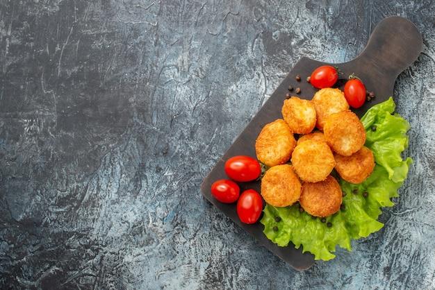 Vista superior bolinhas de queijo frito, tomate cereja, alface em uma tábua na mesa