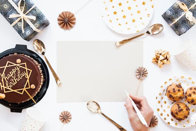 Vista superior bolo de aniversário e biscoitos com convite de aniversário vazio