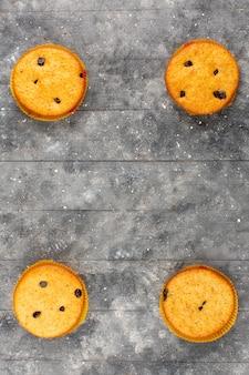 Vista superior bolos amarelo cozido gostoso no chão rústico de madeira cinza