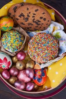 Vista superior, bolos e ovos doces de páscoa em uma cesta. close-up de comida tradicional de páscoa.