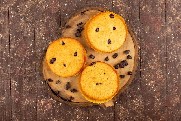 Vista superior bolos redondos deliciosos no marrom de madeira rústico