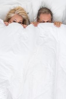 Vista superior bonito casal escondido debaixo do cobertor