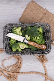 Vista superior brócolis e faca na cesta perto do saco de carvão e corda