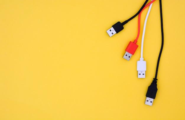 Vista superior cabos usb de cor preta, branca e vermelha em fundo amarelo